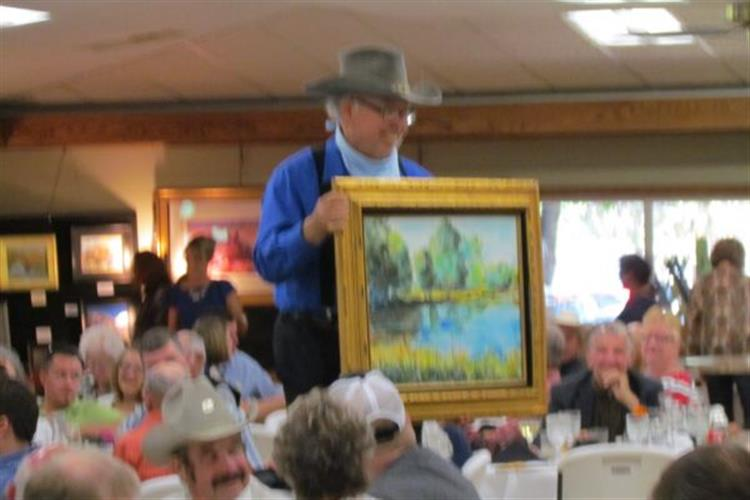 Artist Andrew Watson displays his plein air piece to auction guests