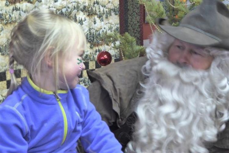 Cowboy Claus chats with a rural kid sitting on top of the museum's antique saddle, to hear what she wants for Christmas.