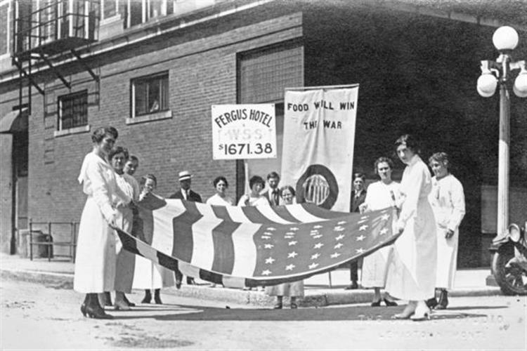 Women holding American flag and banners celebrating funds raised for war effort, Lewistown, Montana, ca. 1918.